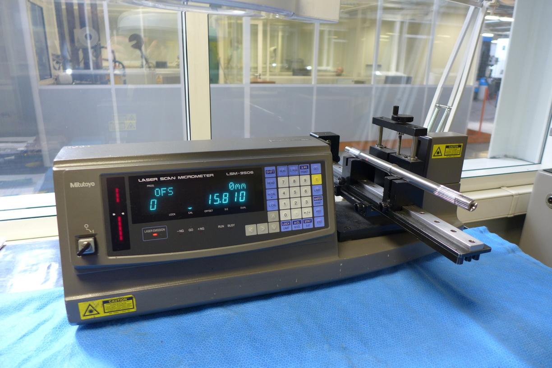 Micromètre laser MITUTOYO pour contrôler le diamètre des pièces mécaniques au micron près. La pièce, ici une tige, est posée sur 2 vés. On applique une rotation manuelle à la tige, le laser détecte les fluctuations de diamètre et les affichent sur l'écran digital.